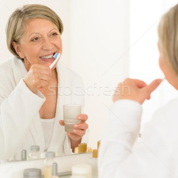 Idős nő fogmosás fürdőszoba tükör tükröződés Stock fotó © CandyboxPhoto