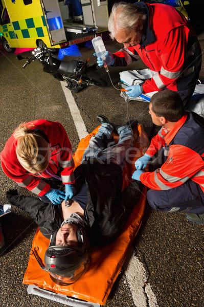 Csapat segít sebesült motorkerékpár sofőr férfi Stock fotó © CandyboxPhoto