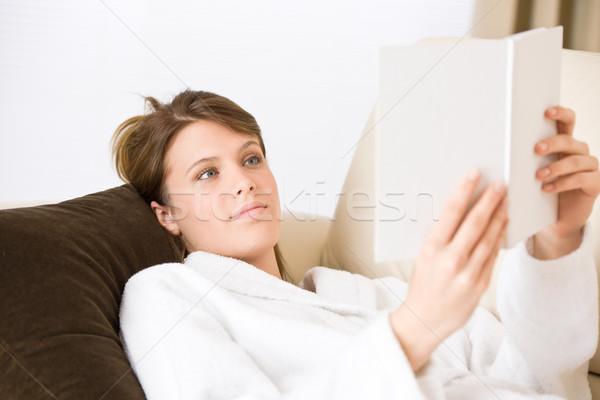 Stock photo: Young woman read book on sofa wearing bathrobe