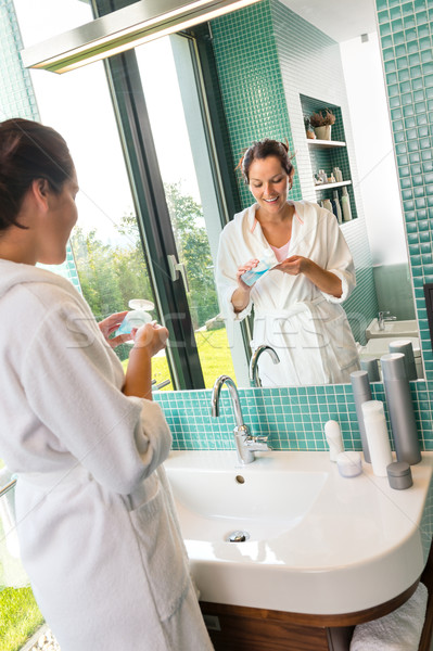 Smiling woman using skin care lotion bathroom Stock photo © CandyboxPhoto