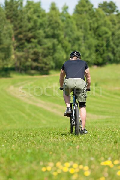 Sportive man mountain biking downhill sunny meadows Stock photo © CandyboxPhoto