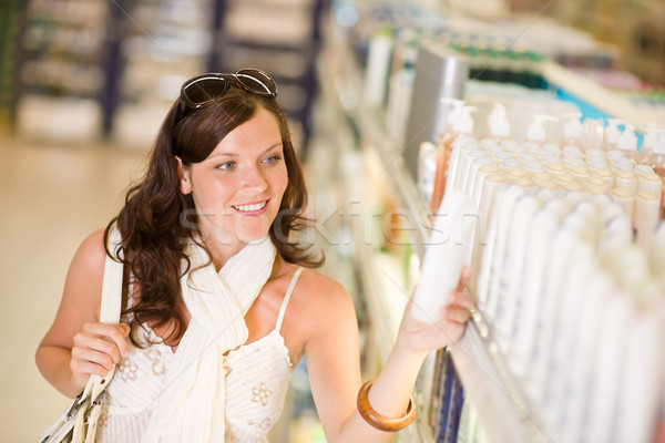 Stock photo: Shopping cosmetics - smiling woman choose shampoo
