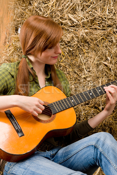 Young country woman playing guitar in barn Stock photo © CandyboxPhoto