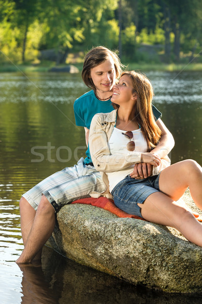Stock photo: Smiling couple sitting on a rock romantic