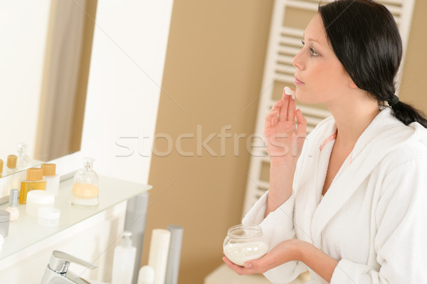 Woman apply face cream looking bathroom mirror Stock photo © CandyboxPhoto