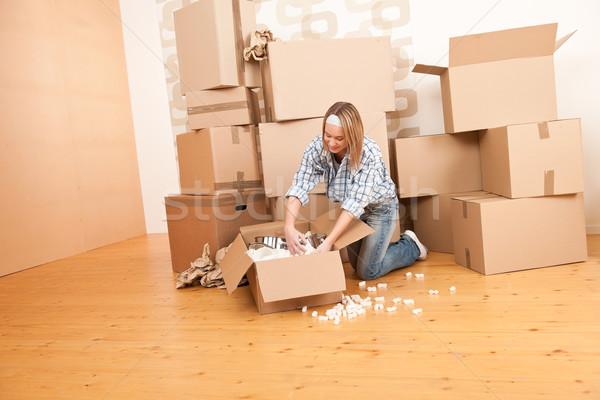 Moving house: Happy woman unpacking box Stock photo © CandyboxPhoto
