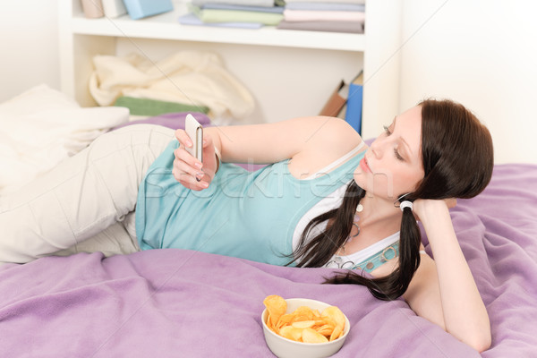 Young student lying on bed eat chips Stock photo © CandyboxPhoto