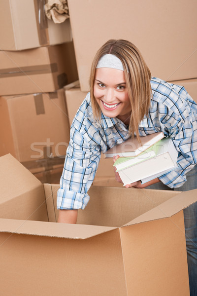 Moving house: Woman unpacking box with book Stock photo © CandyboxPhoto