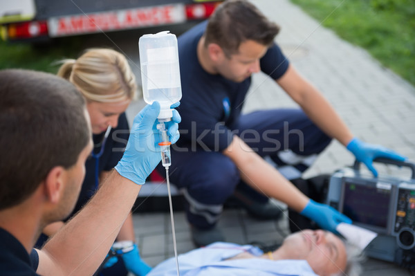 Paramedic holding drip while helping man Stock photo © CandyboxPhoto