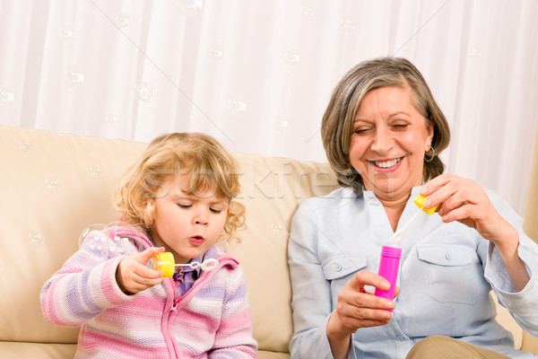 Little girl with grandmother play bubble blower Stock photo © CandyboxPhoto