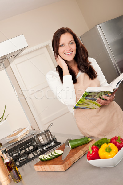 Smiling woman holding cookbook  in the kitchen Stock photo © CandyboxPhoto