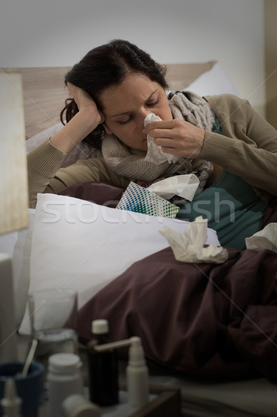 Sick woman with flu sneezing in bed Stock photo © CandyboxPhoto