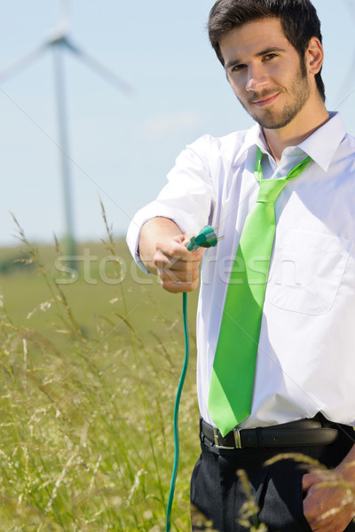 Green energy businessman in field hold plug Stock photo © CandyboxPhoto