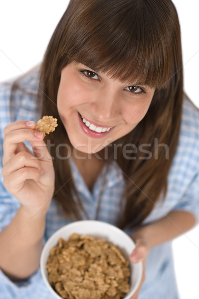 Stock photo: Smiling female teenager eat healthy cereal for breakfast