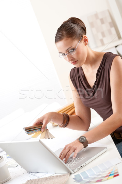 Stock photo: Smiling female designer with color swatch and laptop