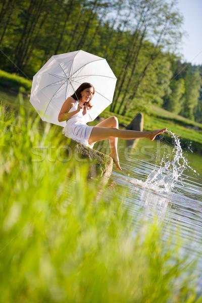Happy romantic woman sitting by lake splashing water Stock photo © CandyboxPhoto