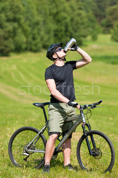 Stock photo: Sportive man mountain biking relax sunny meadows