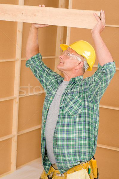 Stock photo: Handyman carpenter mature fitting wooden beam