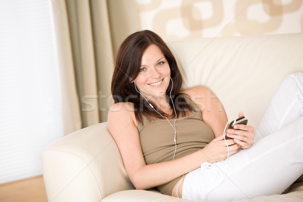 Woman holding music player listening on sofa home Stock photo © CandyboxPhoto