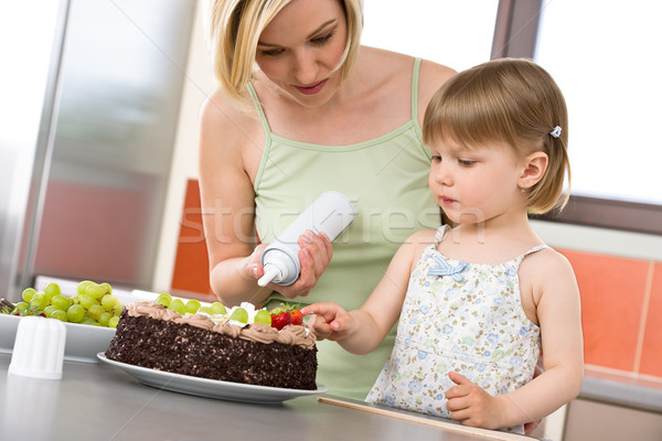 Mother and child with chocolate cake in kitchen Stock photo © CandyboxPhoto