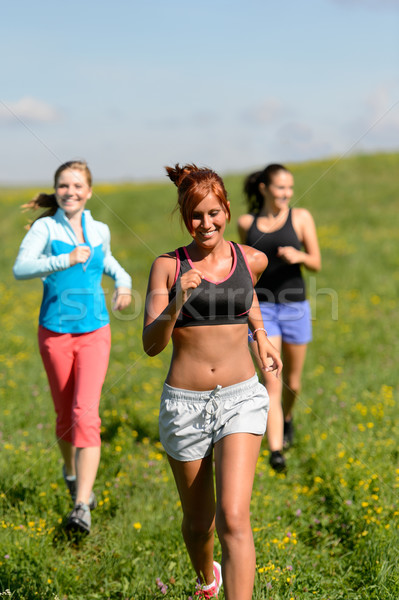 Three girls jogging downhill summer meadow Stock photo © CandyboxPhoto