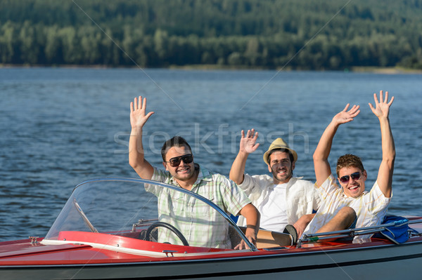 Cheerful young guys partying in speed boat Stock photo © CandyboxPhoto
