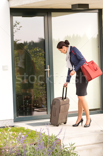 Stock photo: Businesswoman leaving house traveling carrying baggage hurried