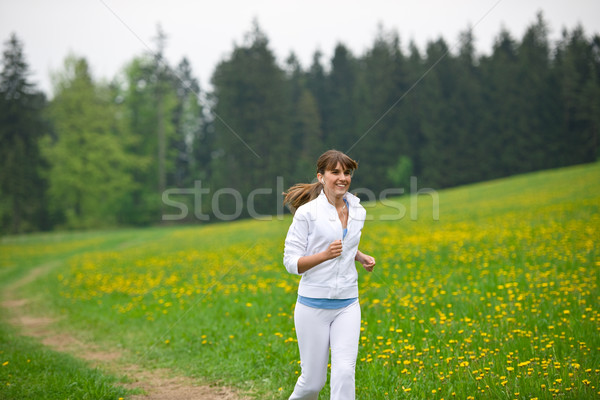 Jogging - sportive woman running in park with dandelion Stock photo © CandyboxPhoto