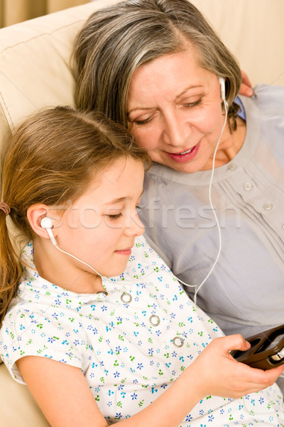 Stock photo: Grandmother and young girl listen music together