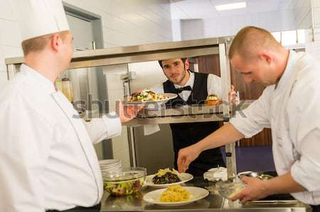 Professional kitchen cook prepare meal give waiter Stock photo © CandyboxPhoto
