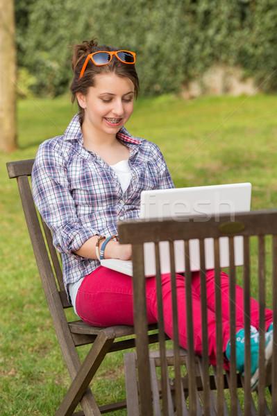 Smiling girl using laptop sitting at park Stock photo © CandyboxPhoto