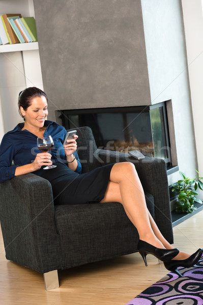 Happy woman relaxing armchair text messaging wine Stock photo © CandyboxPhoto