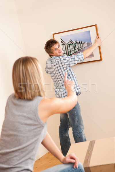 Moving house: Couple hanging picture on wall Stock photo © CandyboxPhoto