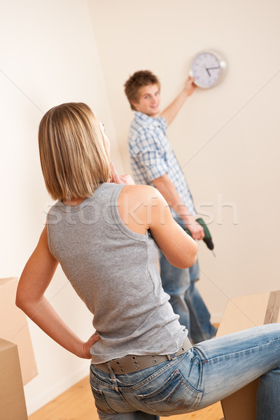 Moving house: Young couple hanging clock on wall Stock photo © CandyboxPhoto