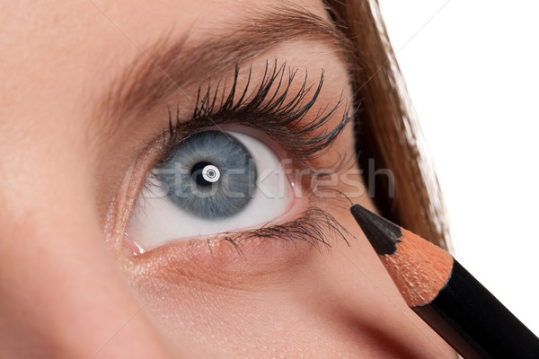 Close-up of blue eye, woman applying black pencil Stock photo © CandyboxPhoto