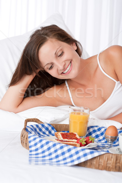 Happy woman in white bed having breakfast Stock photo © CandyboxPhoto