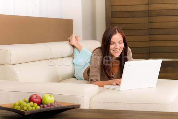 Modern living room woman lying sofa laptop Stock photo © CandyboxPhoto