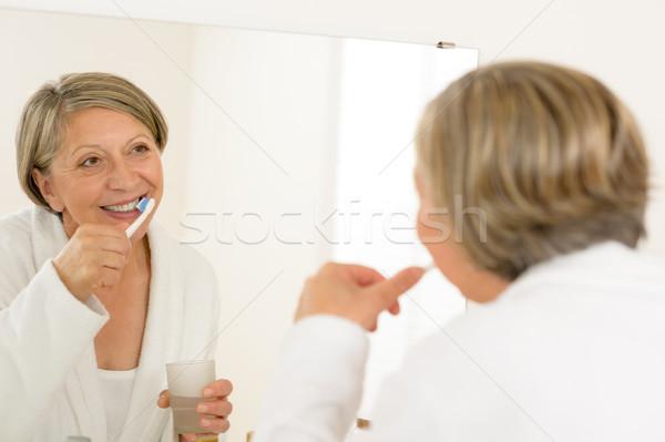 érett nő fogmosás néz fürdőszoba tükör fogkrém Stock fotó © CandyboxPhoto