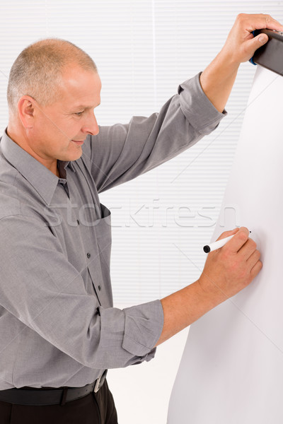 Mature businessman writing at empty flip chart Stock photo © CandyboxPhoto