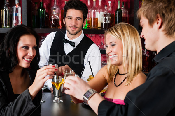Barman behind counter friends drinking at bar Stock photo © CandyboxPhoto
