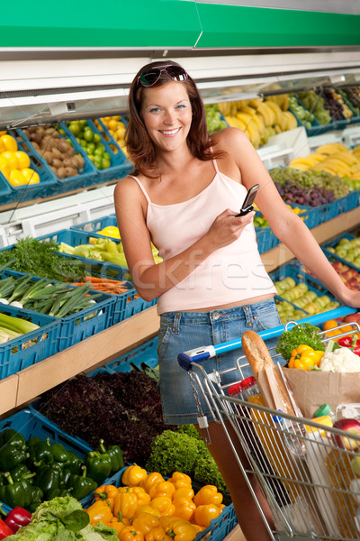 Grocery store shopping - Young woman with mobile phone Stock photo © CandyboxPhoto