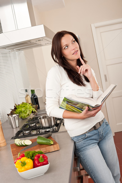 Beautiful woman holding cookbook in the kitchen Stock photo © CandyboxPhoto