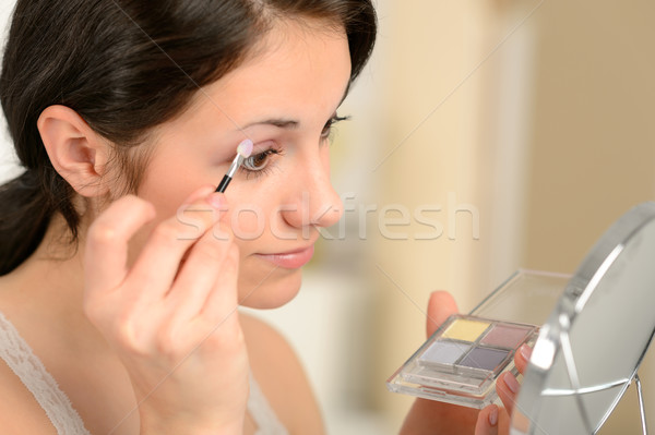 Young girl applying eyeshadow looking at mirror Stock photo © CandyboxPhoto