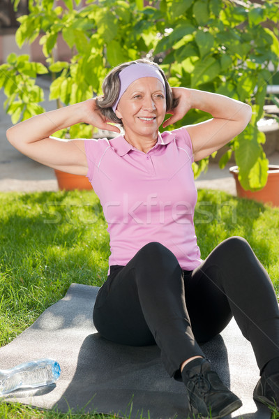 Senior sportive woman doing sit-ups sunny day Stock photo © CandyboxPhoto