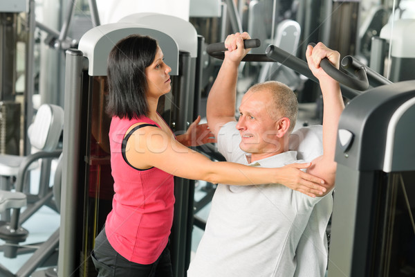 Stock photo: Fitness center trainer assist man exercise back