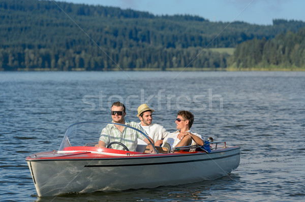 Stock photo: Young men sitting in motorboat scenic landscape
