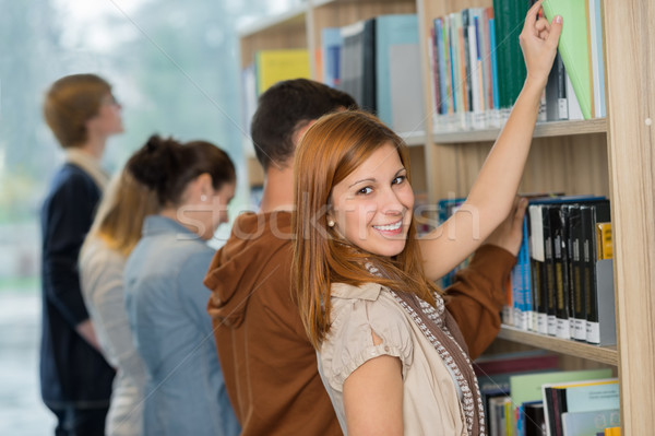 Student choosing book from bookshelf in library Stock photo © CandyboxPhoto