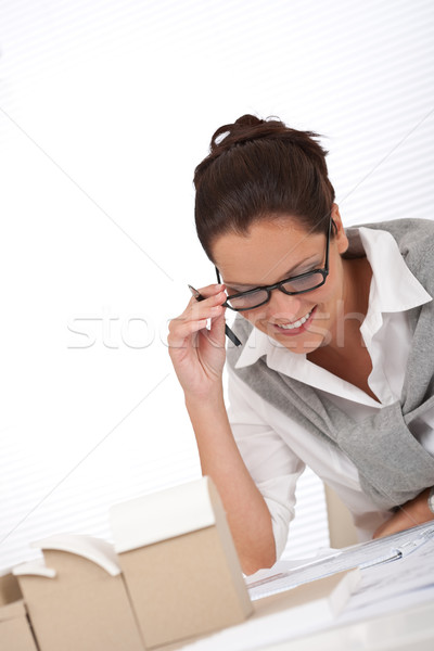 Stock photo: Young female architect writing with pen