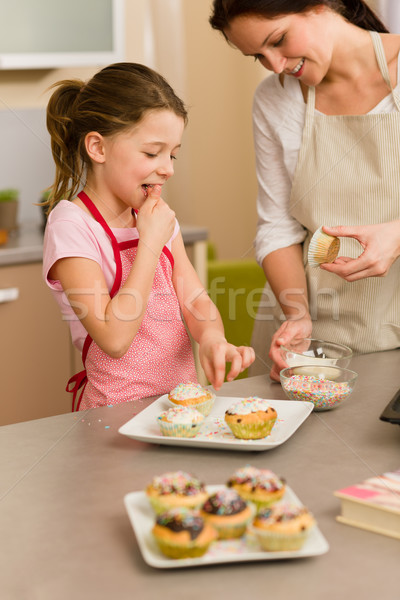 Little girl taste sprinkles decorating cupcake Stock photo © CandyboxPhoto