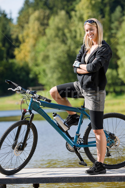 Mountain biking young woman standing by lake Stock photo © CandyboxPhoto